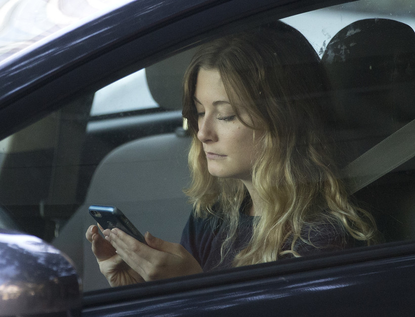 Woman using phone in car