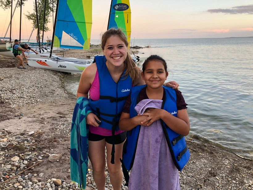 Katie Hermsen and her Little Angelina pose for a photo in front of sail boats