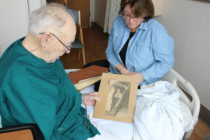 Veteran Ray Miller looks at an old press clipping from his time in the National Guard