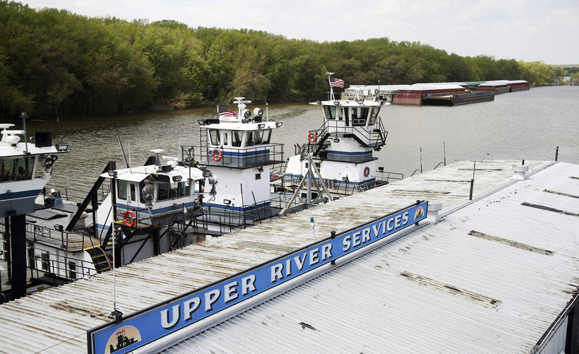 In this Tuesday, May 14, 2019 photo, empty barges, background right, are moored at the Upper River Services along with tug boats on the Mississippi River in St. Paul, Minn., as spring flooding interrupts shipments on the river. Historic Midwest flooding t