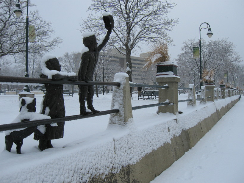 Statues of children greeting riverboats in downtown La Crosse's Riverside Park after snowfall