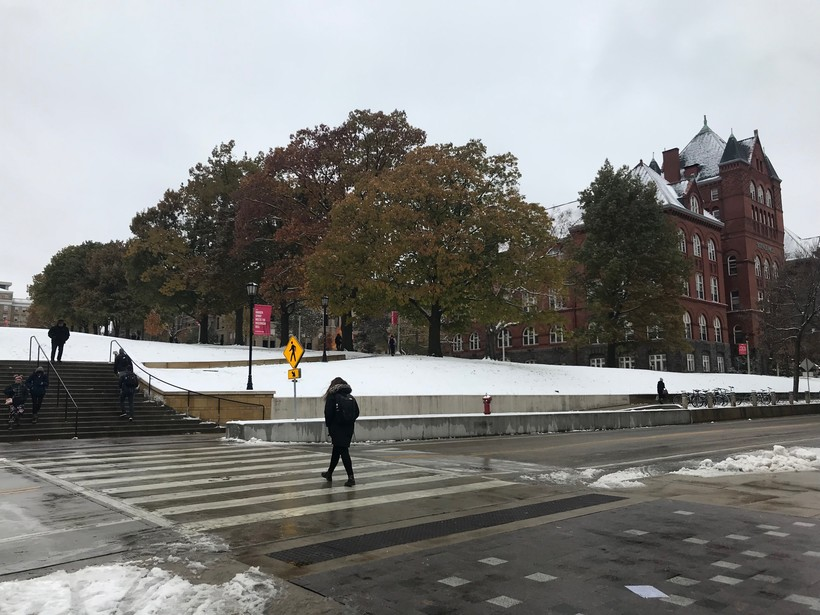 Students cross the street to and from a snowy quad, where the trees still have colorful autumn leaves.