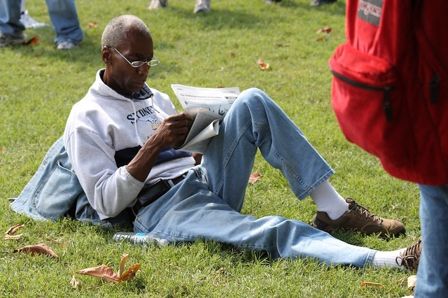 Black man reading newspaper on the lawn