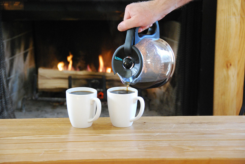two cups of coffee being filled in front of a fireplace