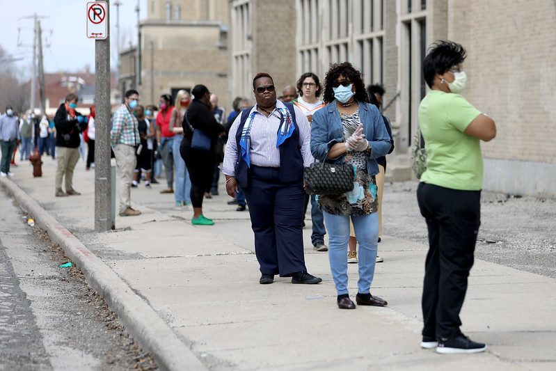 Voters with masks on in line to vote
