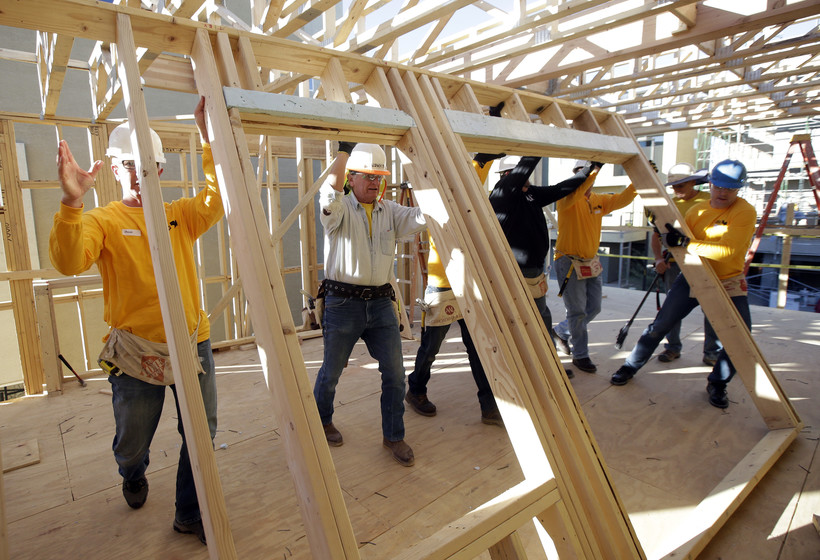 construction workers raise wall of a new home