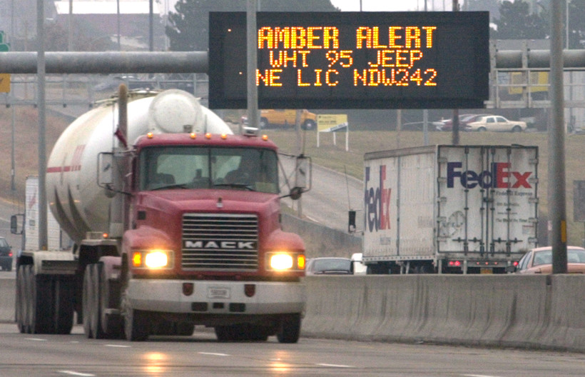 Electronic signs flash with an amber alert over Interstate 80 in Omaha, Neb.