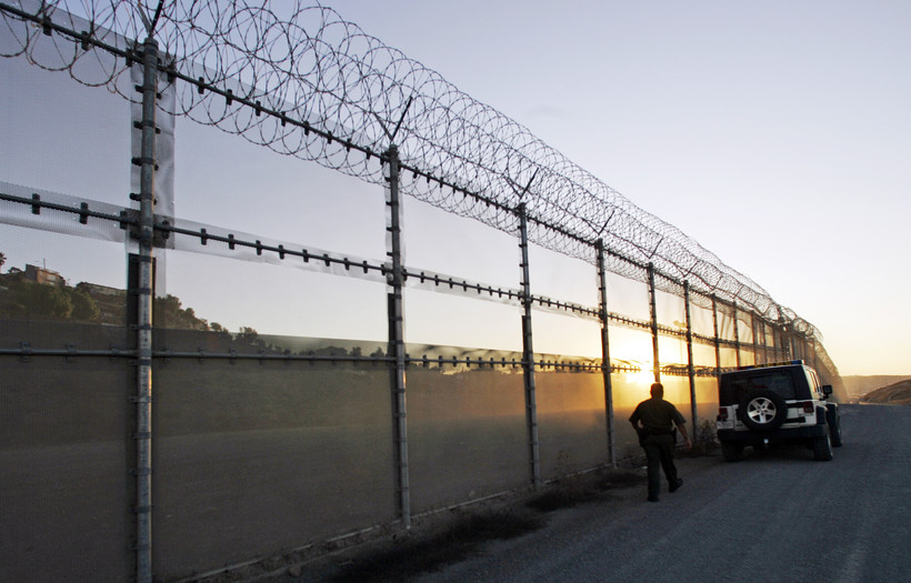 U.S. Border Patrol agent walking back to his vehicle along the border fence in San Diego, California.