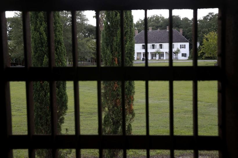 A plantation house seen through bars