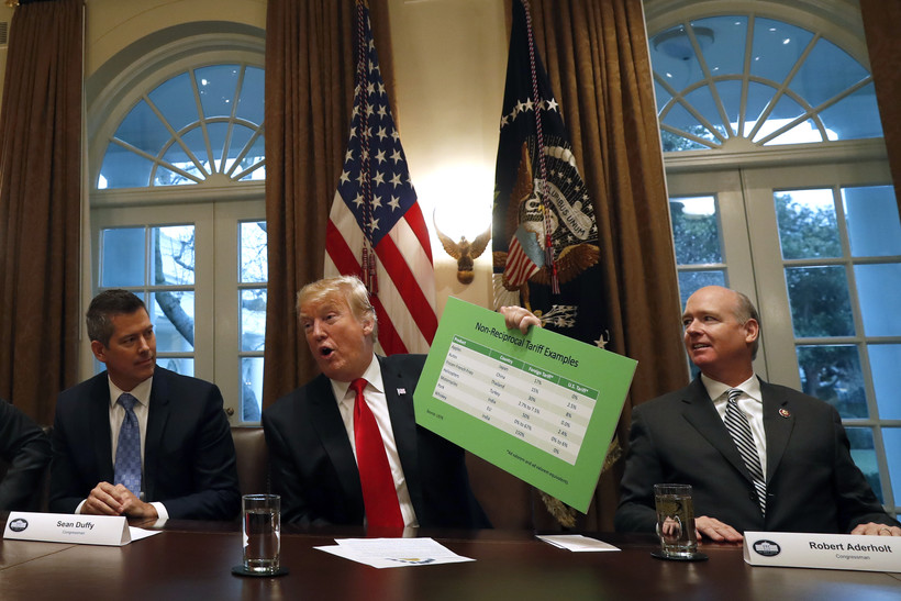 President Donald Trump holds up examples of tariffs