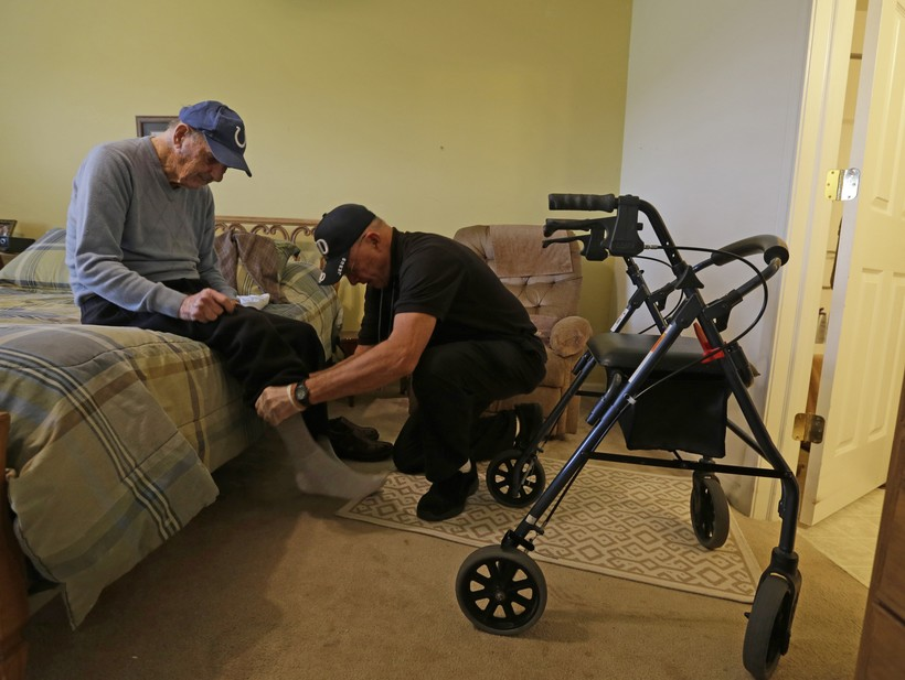 A caregiver helps an elderly man get dressed