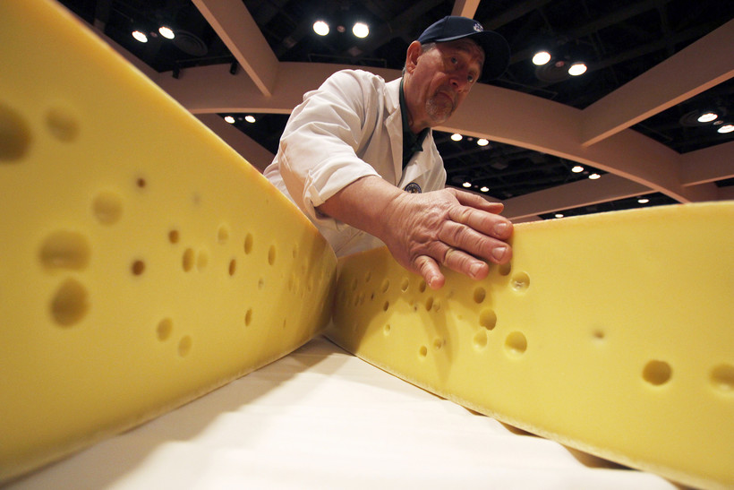 A man inspects Swiss cheese at the World Championship Cheese Contest
