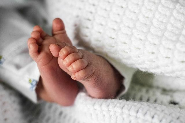Close-up of infant feet swaddled in blanket