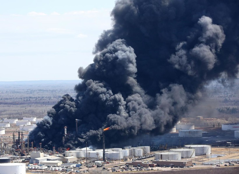 A plume of darks smoke rises from the refinery fire