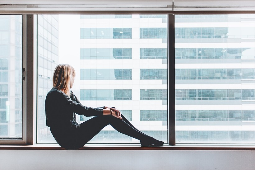 A woman sits on a ledge and looks out the window
