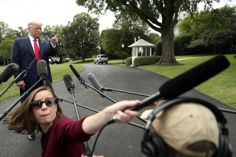 President Donald Trump points to a reporter for a question as he speaks to members of the media.