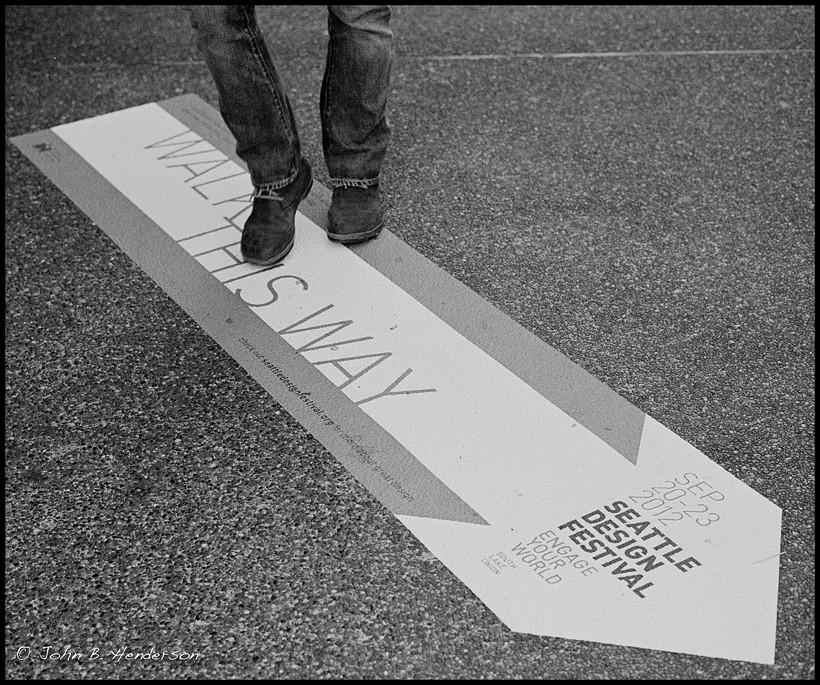 "feet walking on ""Walk This Way"" sign"