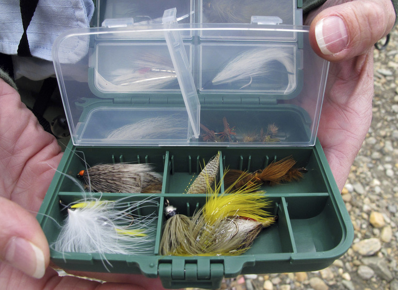 A fly fishing guide displays a box of flies during a fly fishing retreat