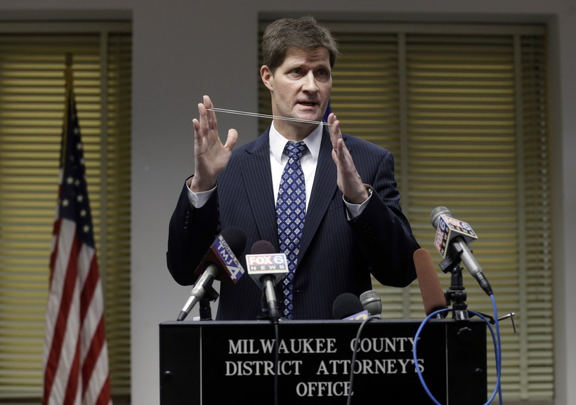 Milwaukee County District Attorney John Chisholm demonstrates bullet trajectory.