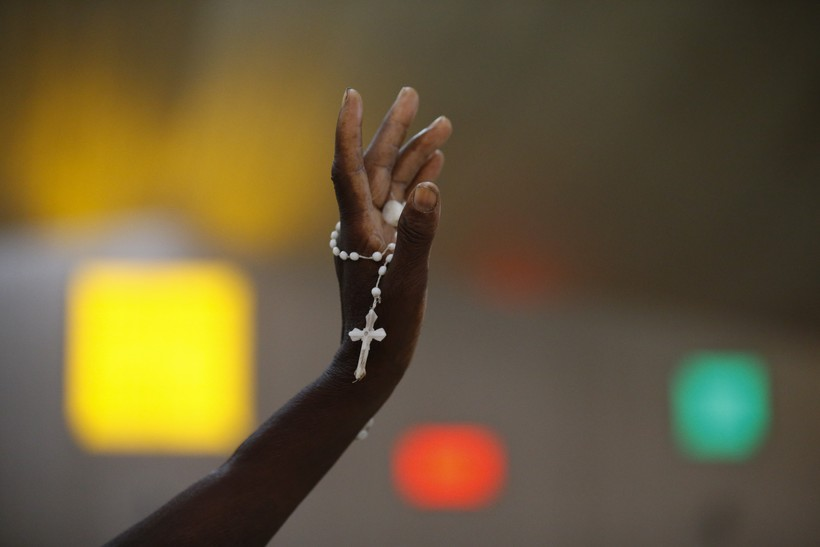 A hand holding a rosary
