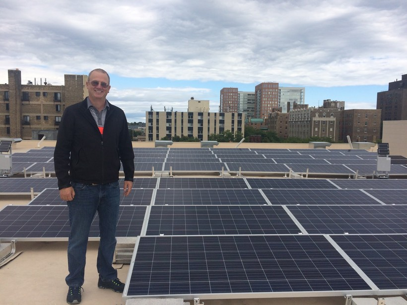 Mike O'Connor stands next to solar panels
