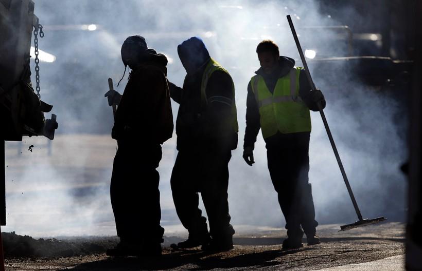 Workers standing next to hot asphalt mixture