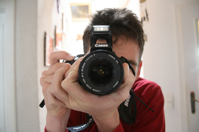 man holding a SLR camera
