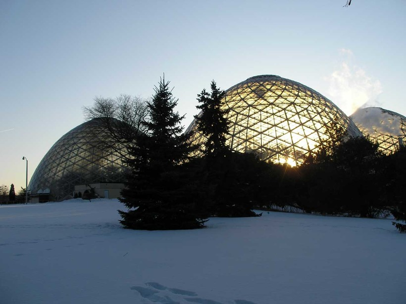 Glass domes with sunlight behind them, in winter landscape