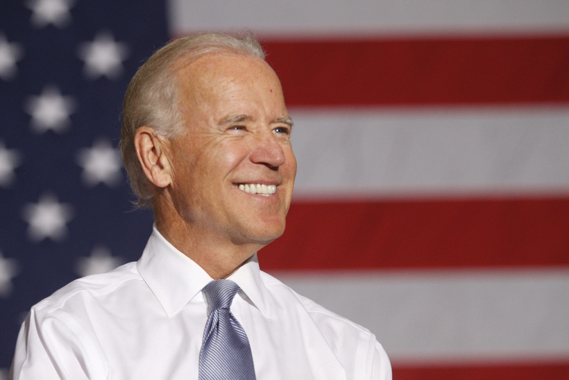 Joe Biden smiles in front of an American flag