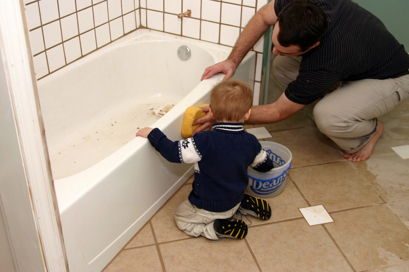 Father and son cleaning bathtub with sponge