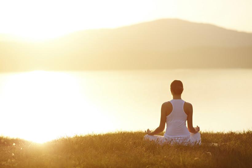 Woman meditating near water