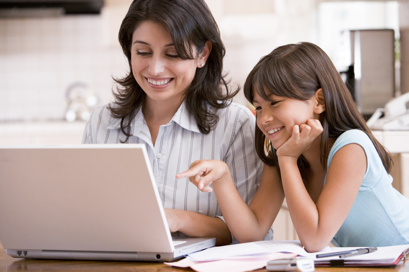 Woman and young girl looking at computer.