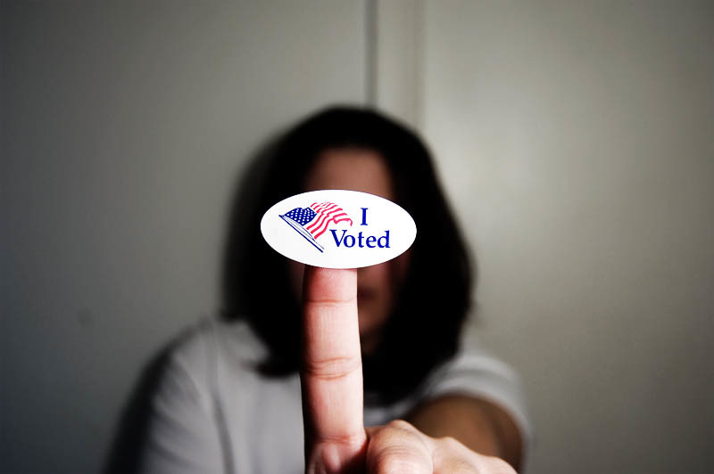 Women holding an I Voted sticker