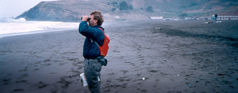 man staring out at ocean with binoculars