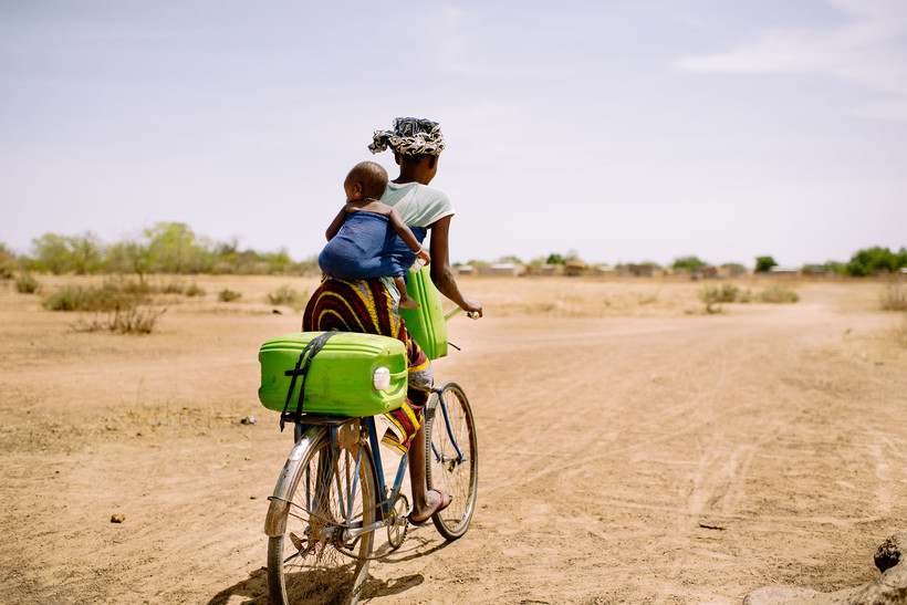 Mother getting water on bike with child riding on back