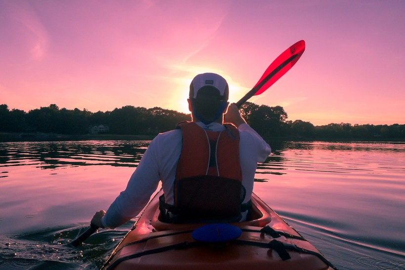 canoe heading into sunset