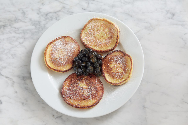 four pancakes with powdered sugar and a pile of blueberries on a white plate on a marble table