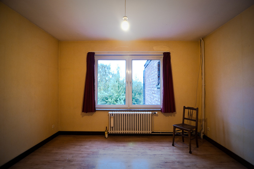 Empty room with radiator and chair