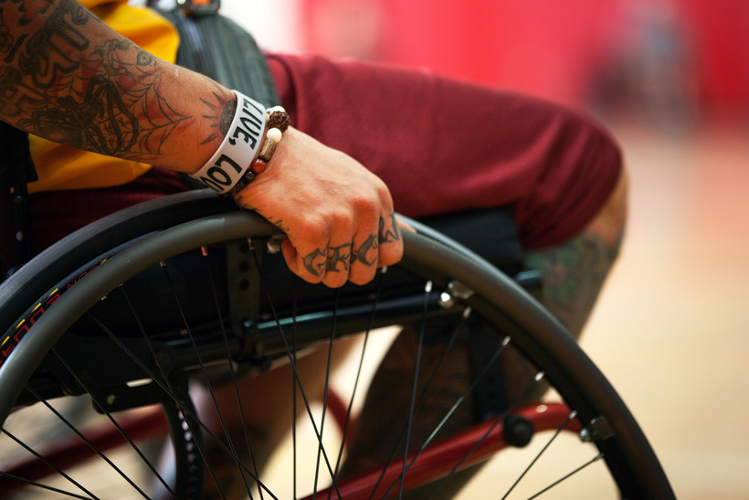 man with tattooed hands sits in a wheelchair