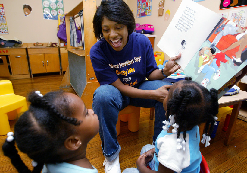 Child care worker reading a book