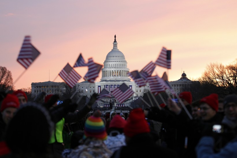 People wave American flags on the National Mall in Washington