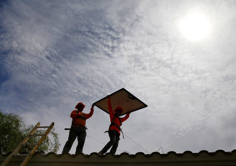 People installing solar panels on a roof