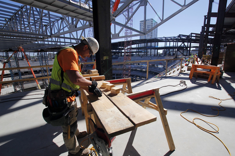 construction workers saws wood at the new milwaukee bucks arena