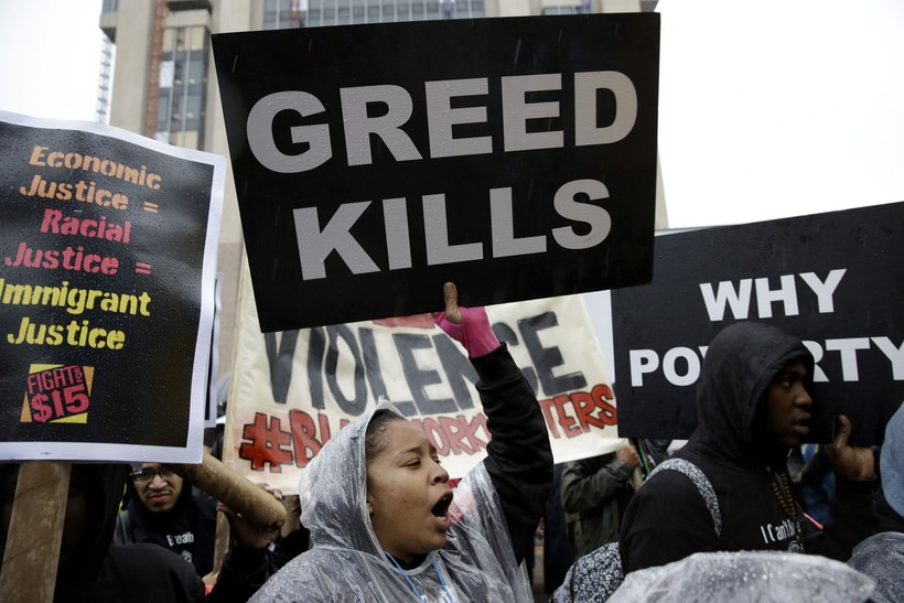 People hold signs and chant slogans during a rally supporting a $15-an-hour minimum wage in New York
