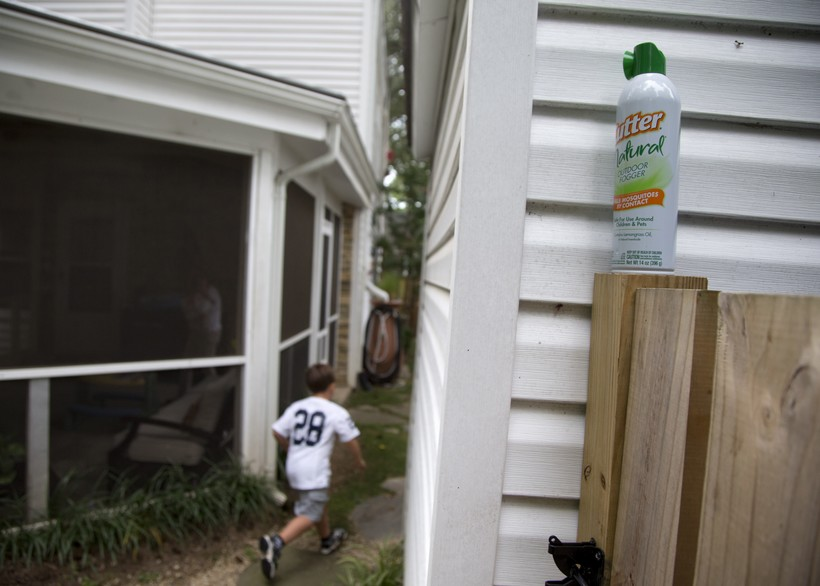 boy runs between homes past bug spray canister