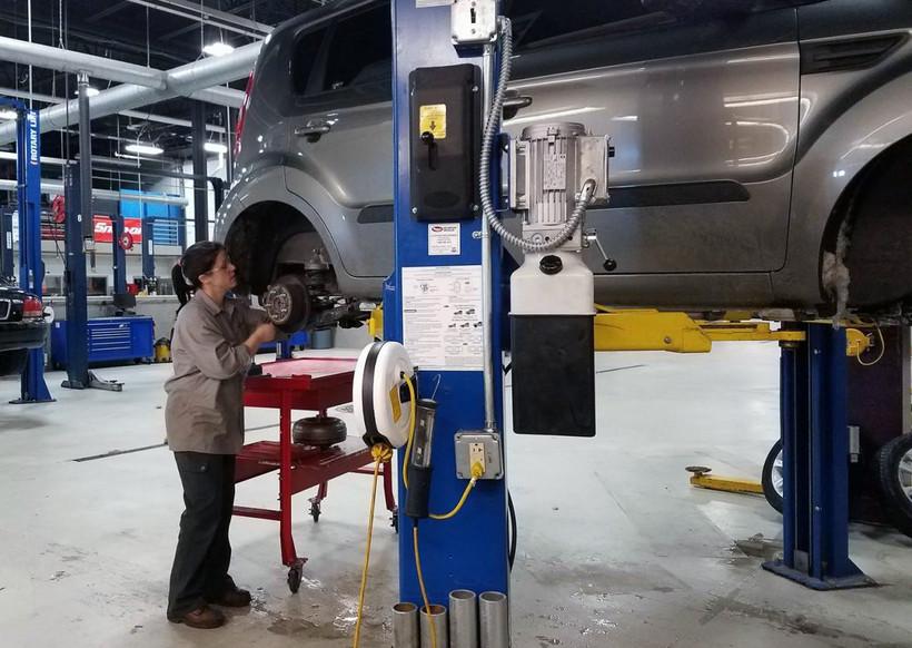 Woman repairing a car.