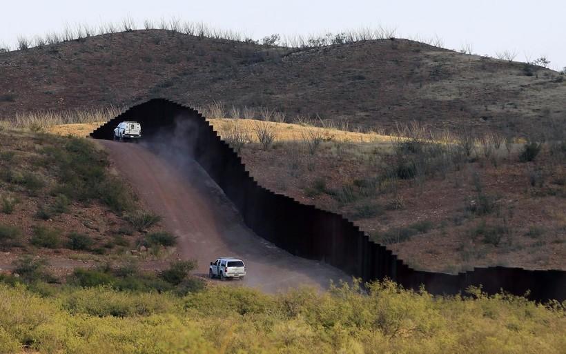 U.S. Border Patrol agents patrol the border fence in Naco, Ariz.