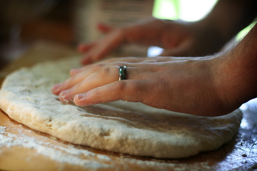 Hands kneading pizza dough