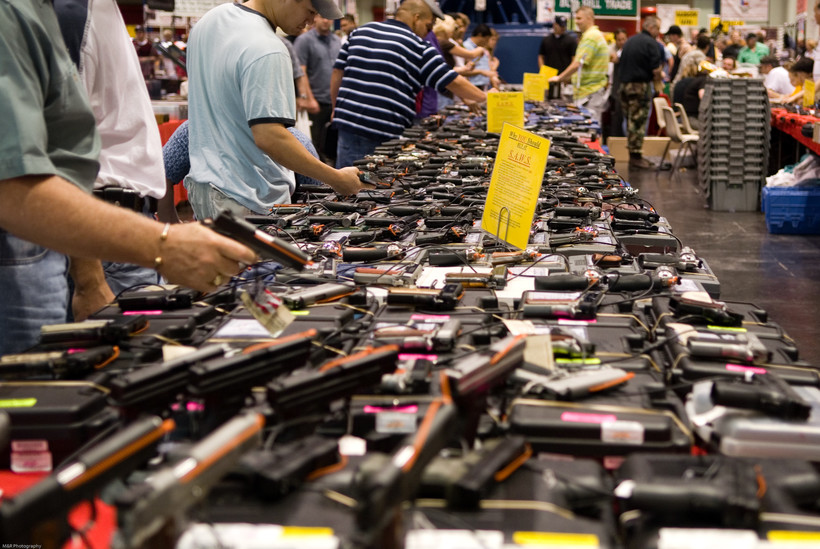 many guns displayed on a table at gun show