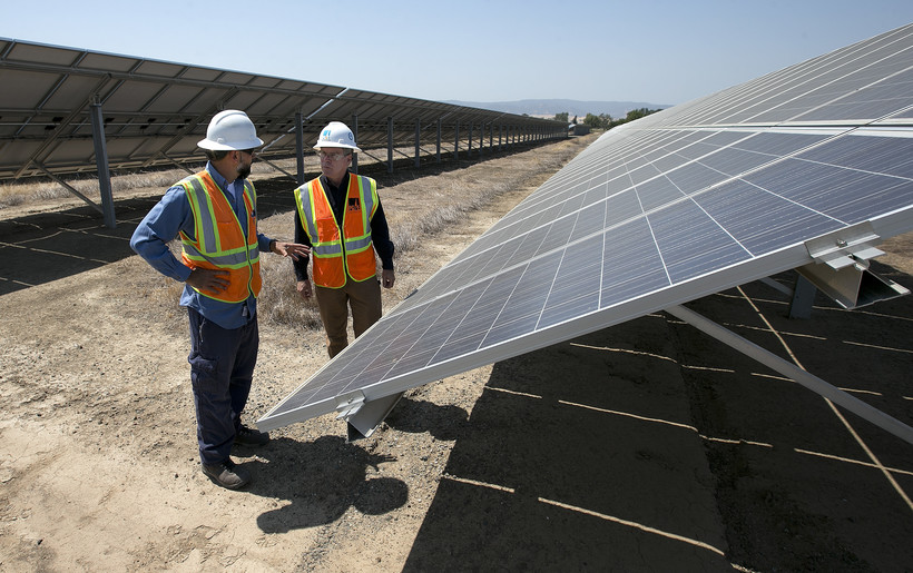 workers stand near solar panels